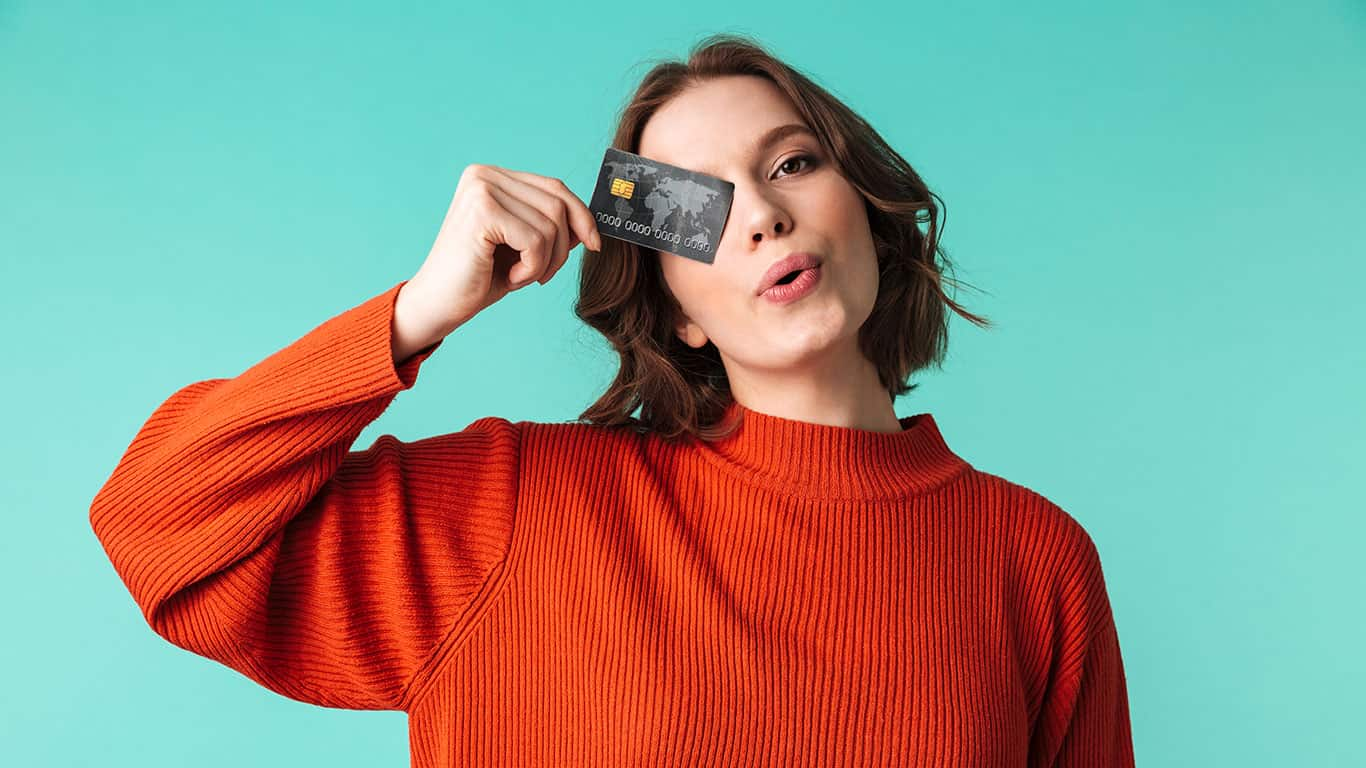 Portrait of a pretty young woman dressed in sweater holding credit card