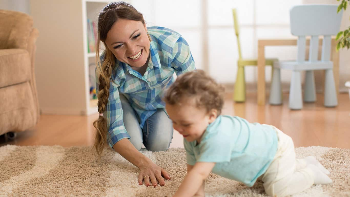 Babysitter and baby toddler playing and having fun time together at home