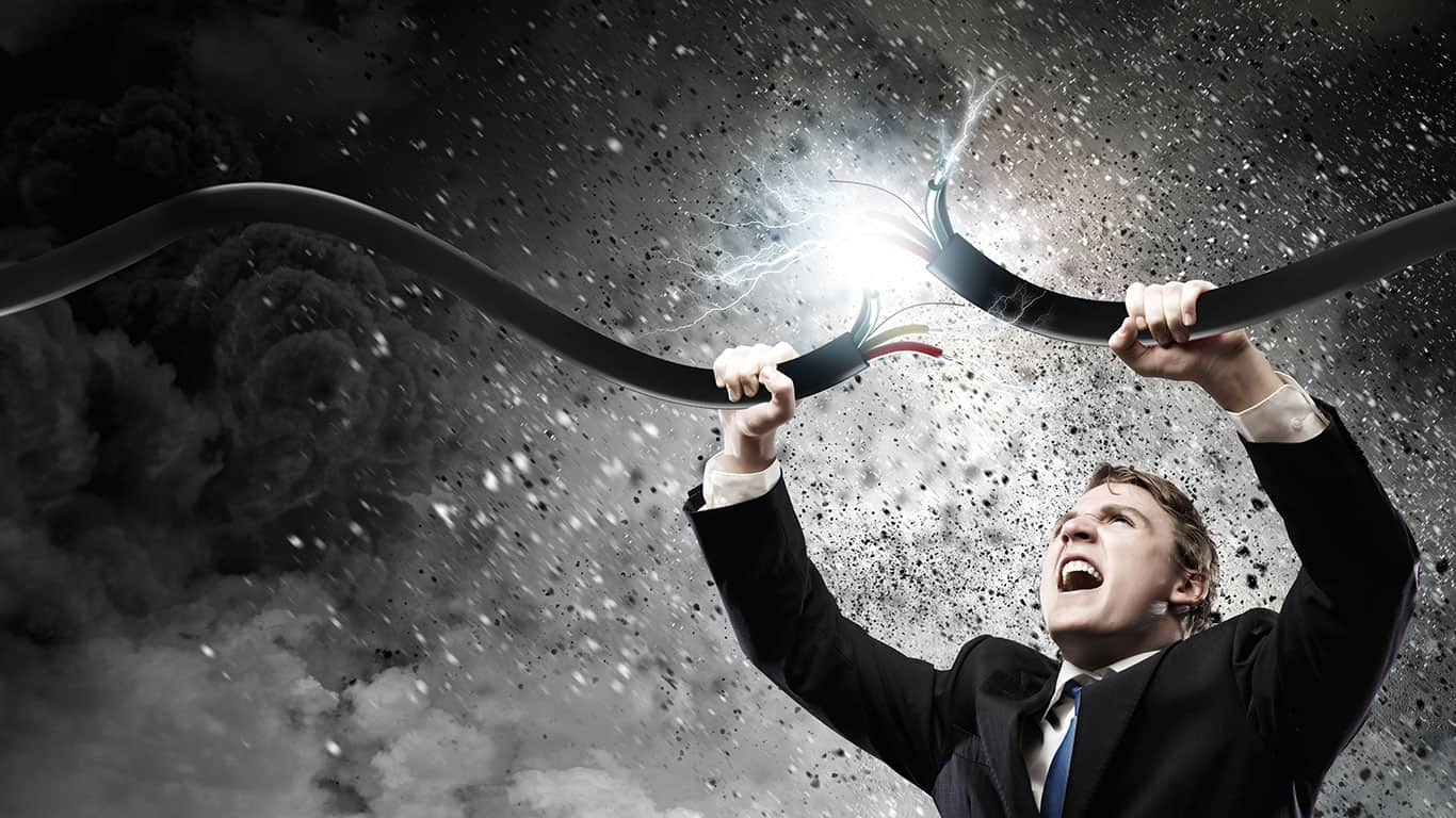 Determined businessman tearing electricity cable with hands