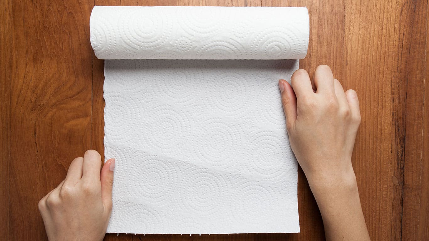 Using a paper towel on a wood surface