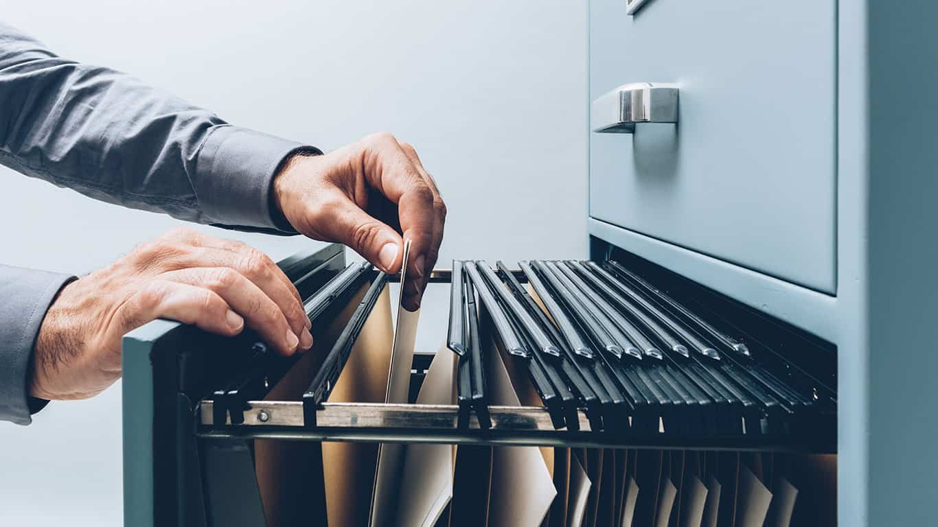 Office clerk searching for files into a filing cabinet drawer close up