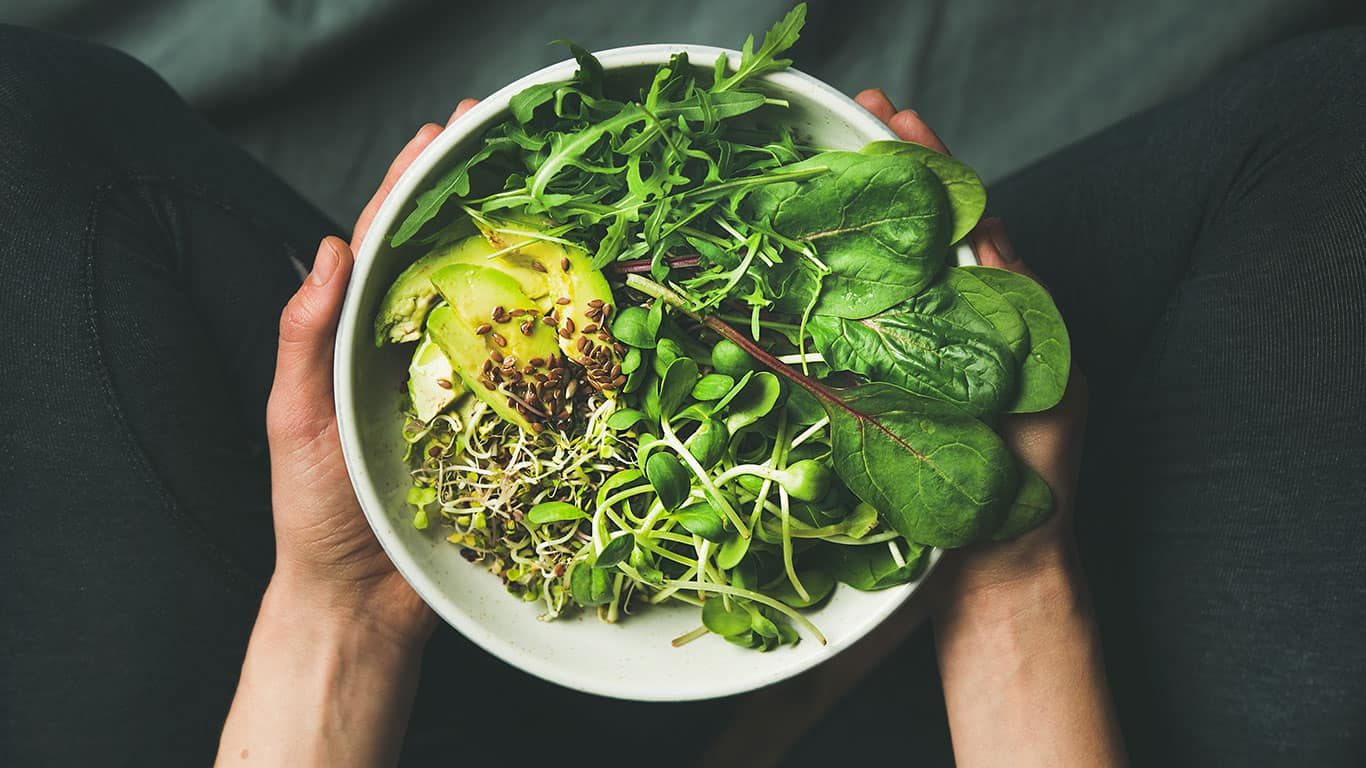 Green vegan breakfast meal in bowl with spinach, arugula, avocado, seeds and sprouts