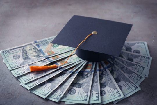Graduation hat and dollar banknotes on table