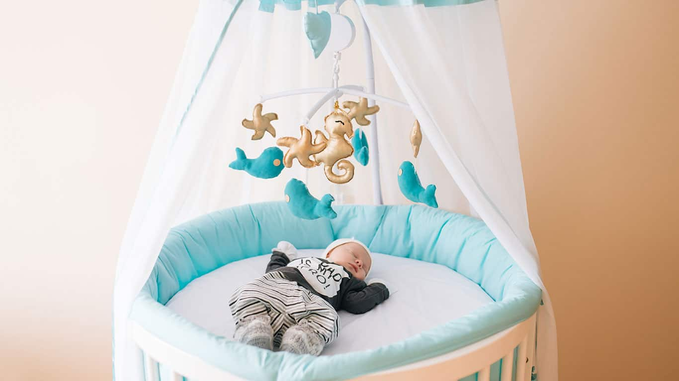 Beautiful newborn baby lying in an oval bed with beautiful bumpers in delicate gray, blue, white tones