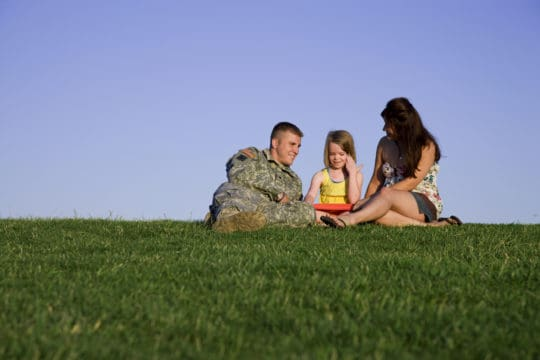 Military family sitting in a park