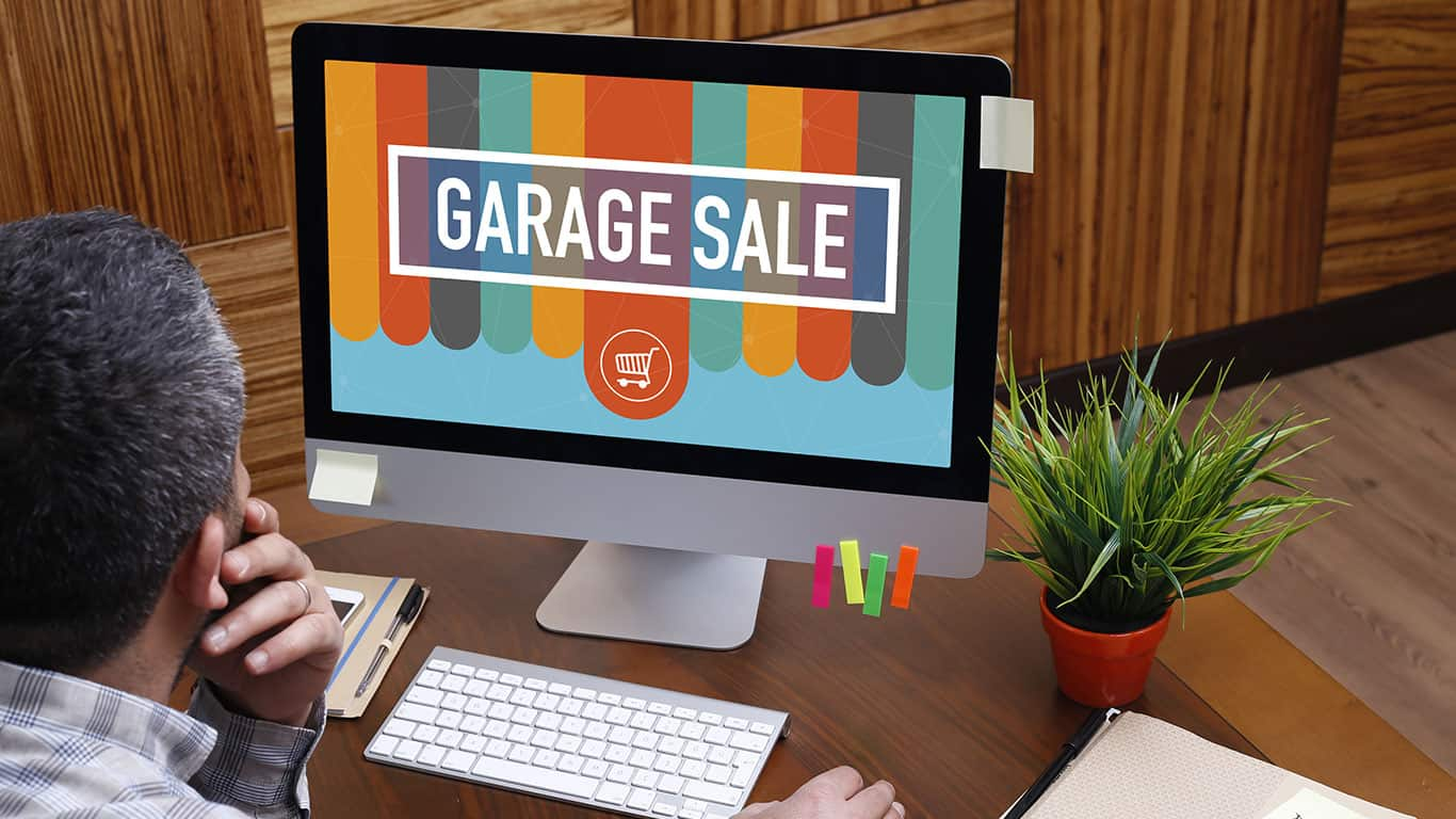 Man using computer with GARAGE SALE concept on screen