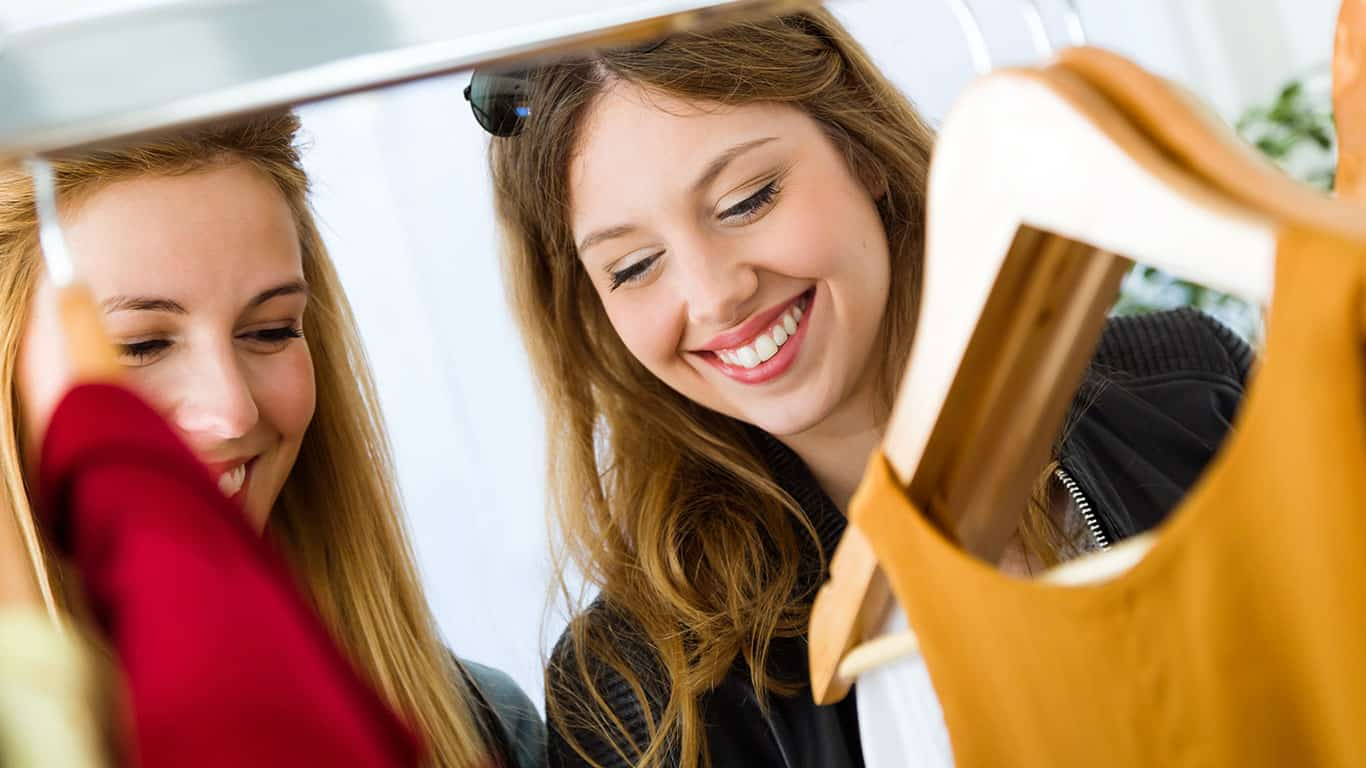 Portrait of two beautiful young women shopping in a clothes shop