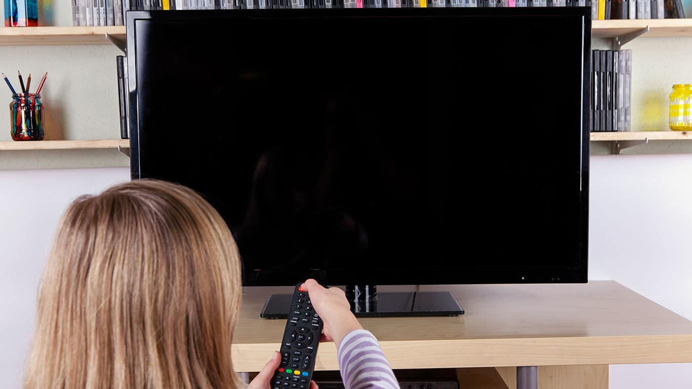 Young girl turning on or off the TV with a remote control