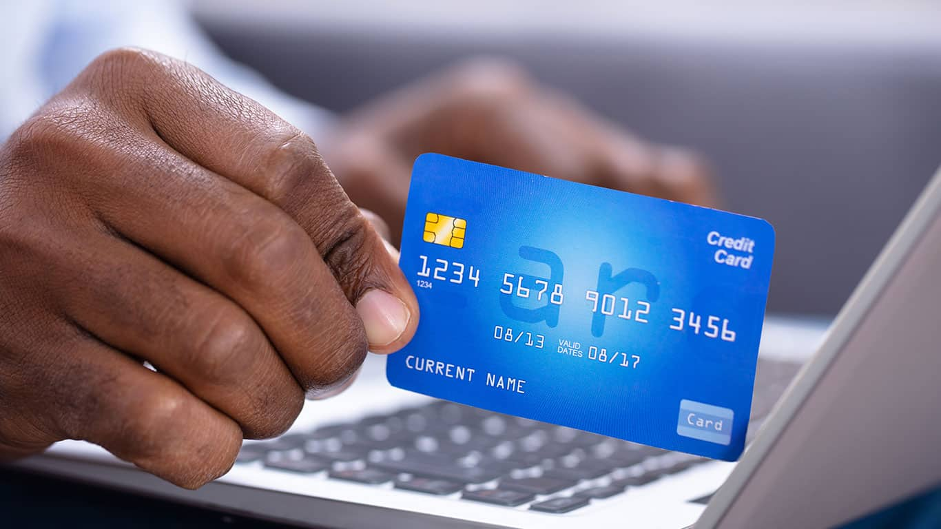 Close-up Of A Man's Hand Holding Credit Card While Using Laptop