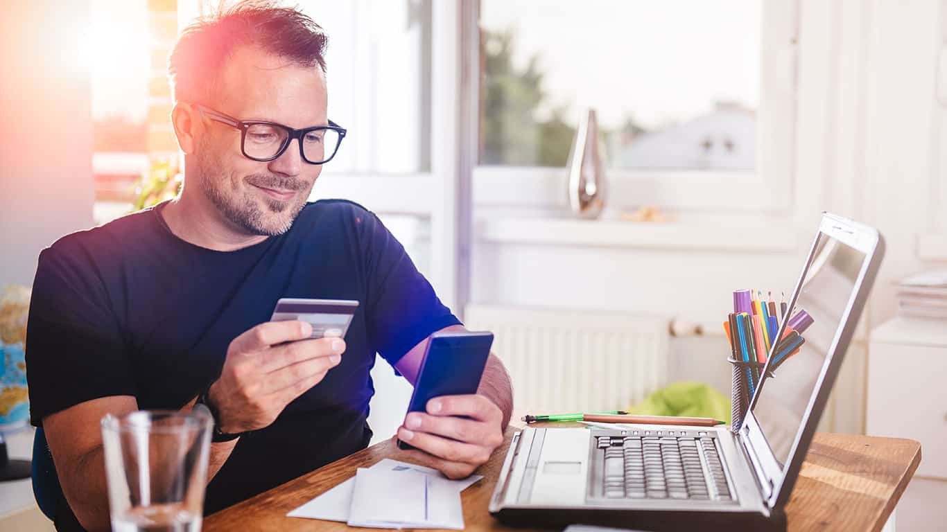 Man paying with credit card on smart phone at home office