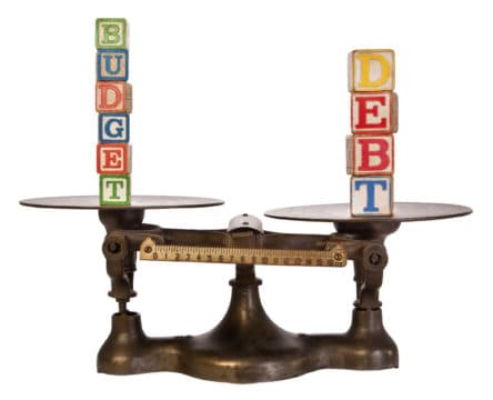 wooden blocks spelling debt and budget balancing on a scale; what is debt?