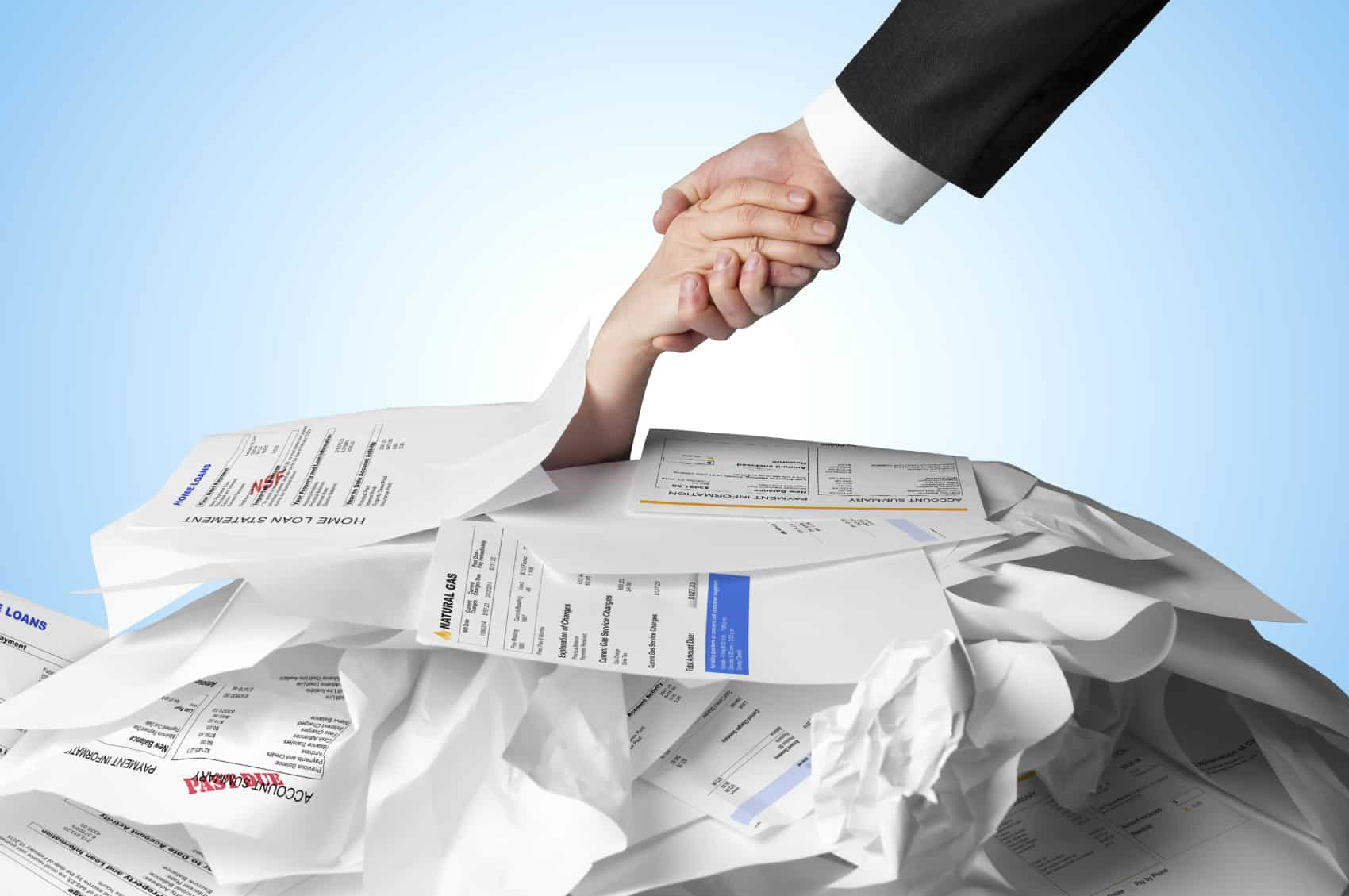 what is debt? Hand being pulled out of pile of debt papers