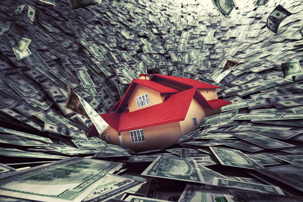 Real estate market crisis with a house sucked into debt