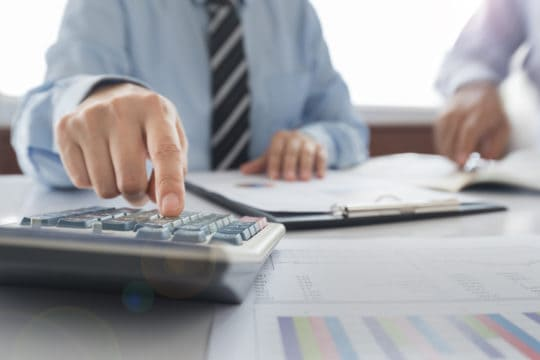 how to settle credit card debt; Businessman using a calculator to calculate the numbers.
