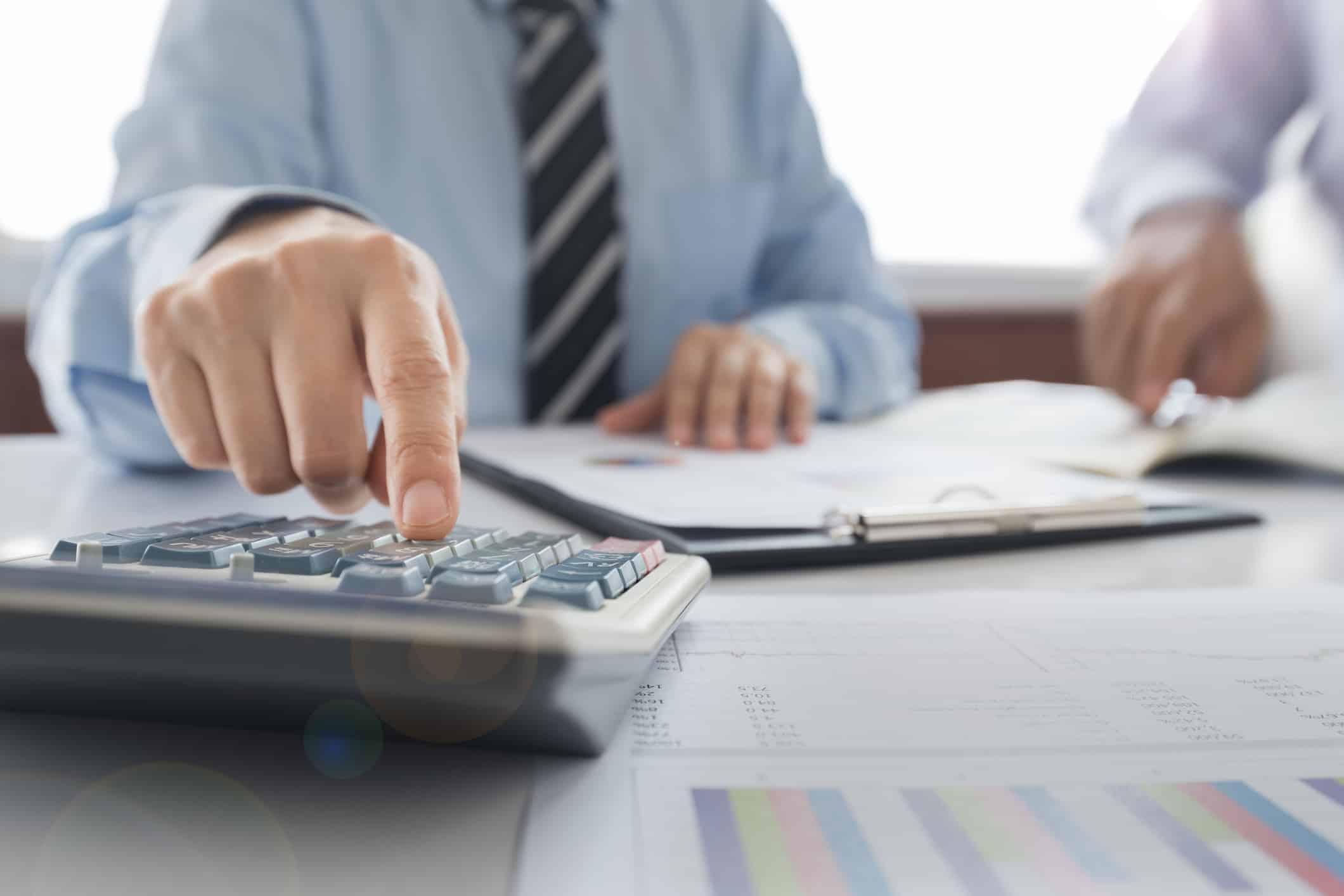 debt consolidation vs debt settlement; business man using a calculator