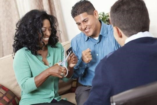 debt consolidation vs debt settlement; woman cutting up credit card with counselor and partner