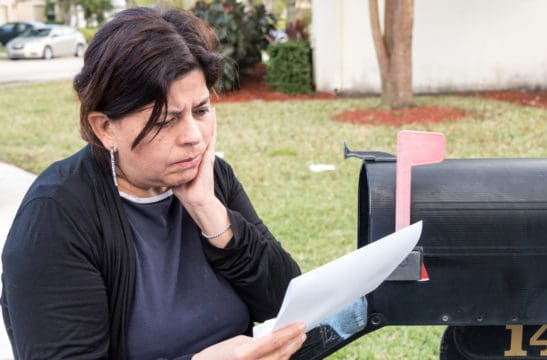 Hispanic mature women reading the mail, very concerning news; debt collections, what is debt