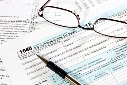 do i have to pay taxes on freelance work?; tax forms with pen and glasses on top
