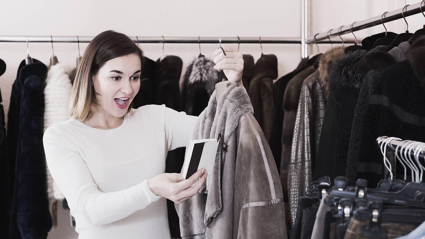 Ordinary girl deciding on warm sheepskin coat in women`s cloths store