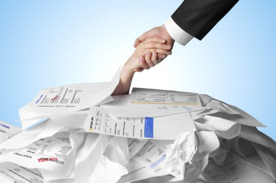 debt consolidation program; hand reaching out of pile of debt papers