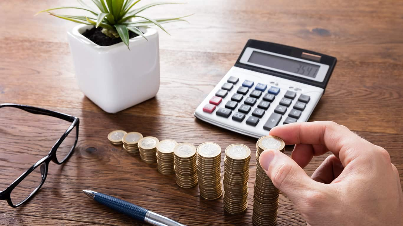 Close-up Of A Person Hand Calculating On Wooden Desk In Front Of Stacked Coins. Income Tax Raise Concept