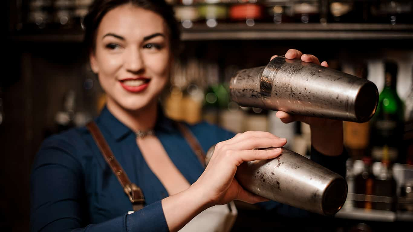 ttractive bartender girl in the white apron holding in her hands two steel cocktail shakers at the bar counter