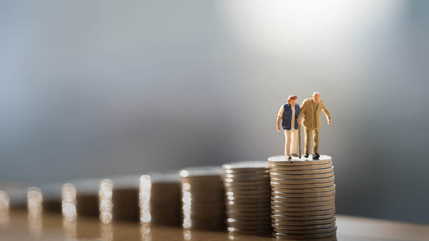 Concept of retirement planning. Miniature people: Old couple figure standing on top of coin stack