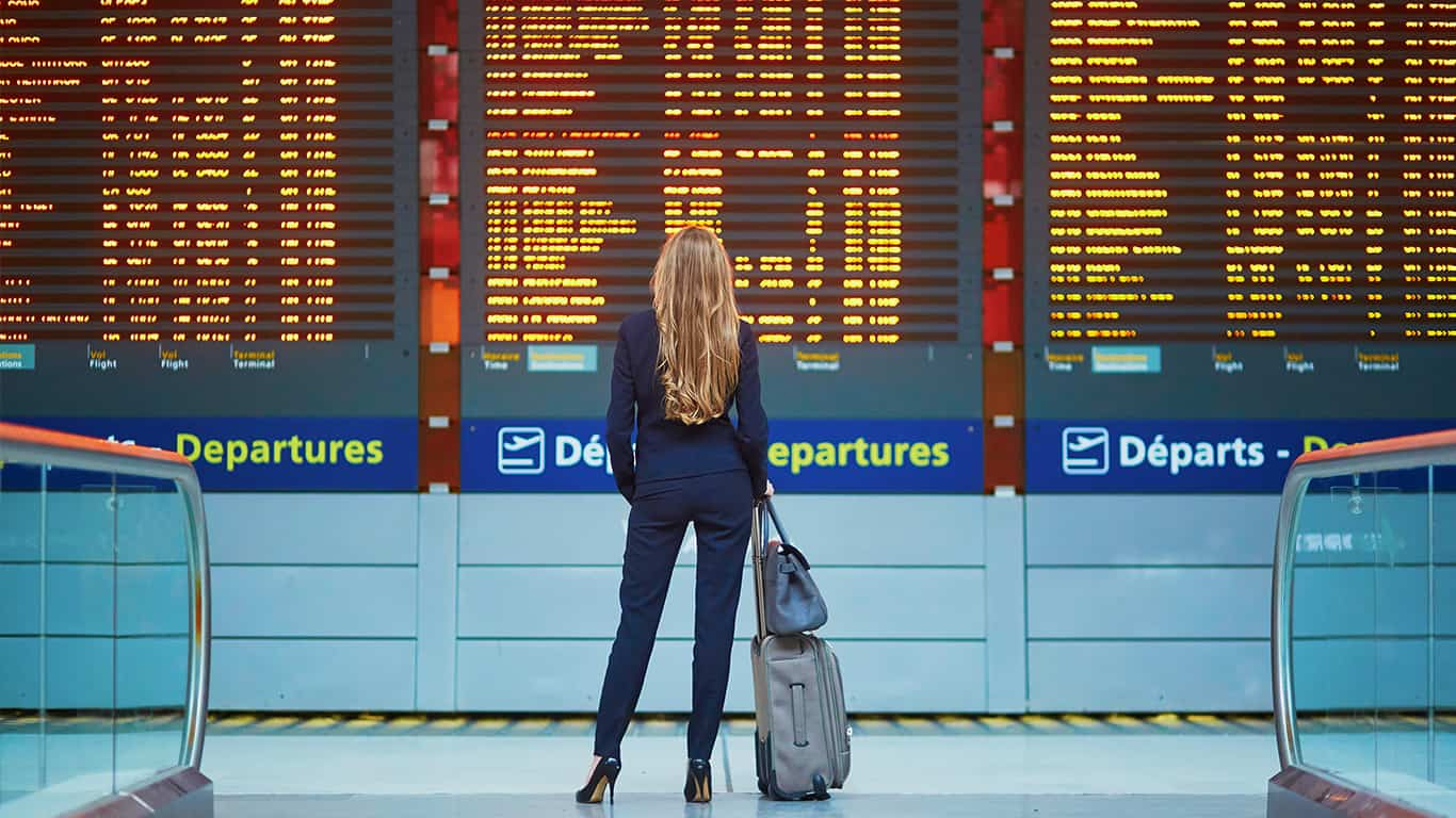 Young elegant business woman with hand luggage in international airport terminal