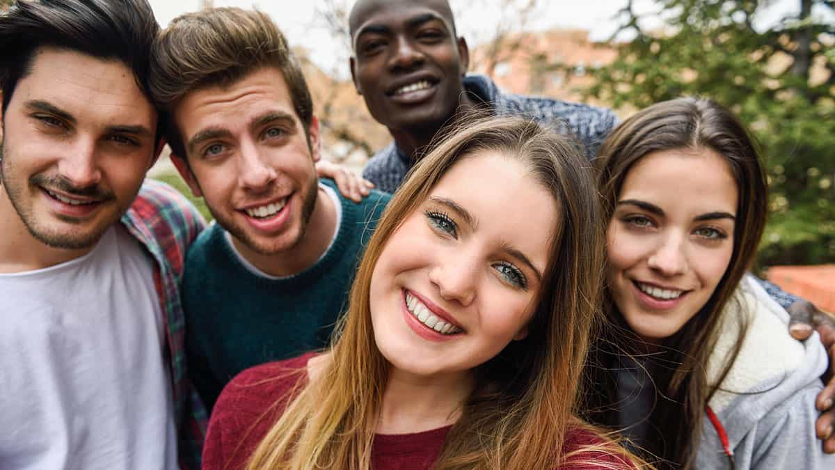 Multiracial group of friends taking selfie in a urban park with a blonde young girl in foreground