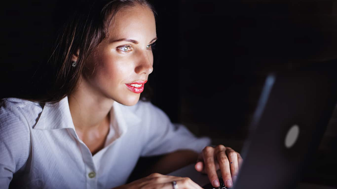 Woman using computer late at night, isolated on black background
