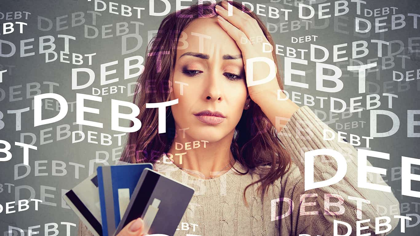 Concerned woman looking at many credit cards scared with huge amount of debt
