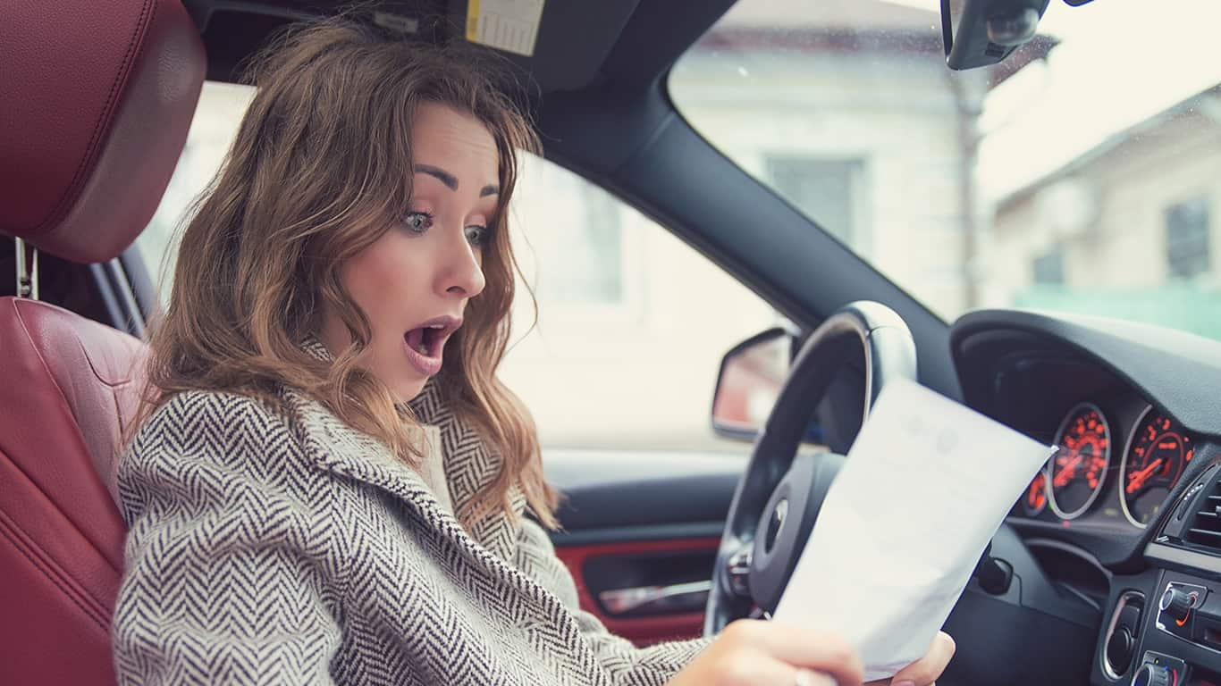 Young girl sitting inside of a car and reading fine papers, looking frustrated