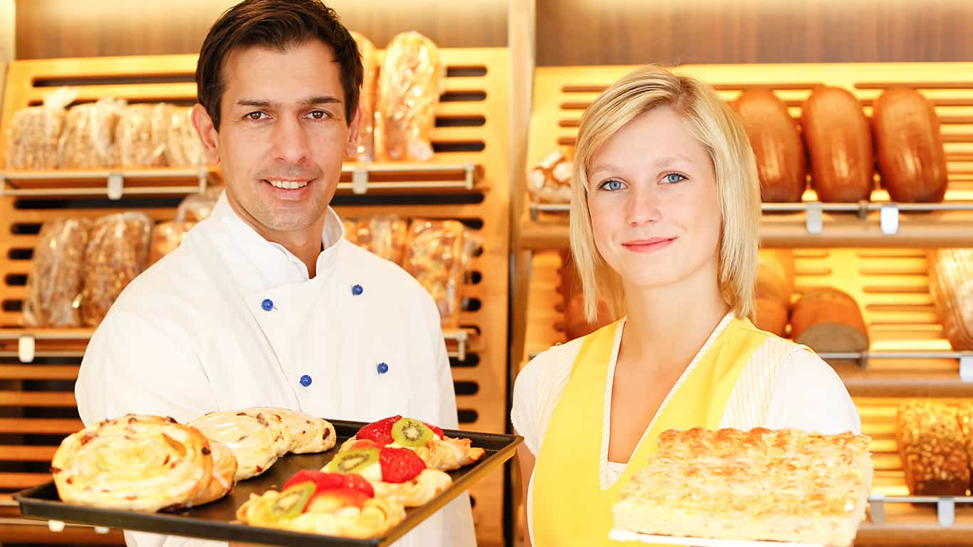 Bakery shopkeeper and baker present different types of pastry in shop