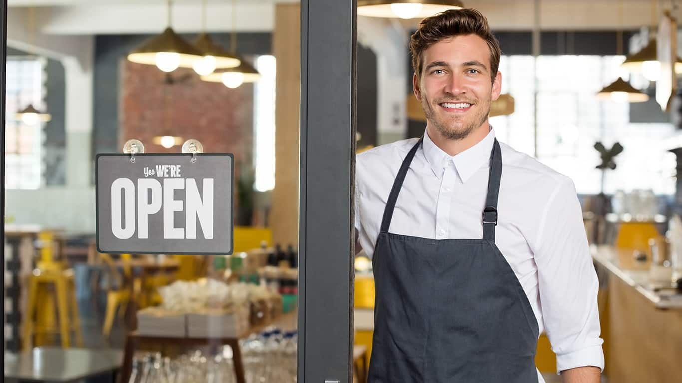 Portrait of smiling owner standing at his restaurant gate with open signboard.