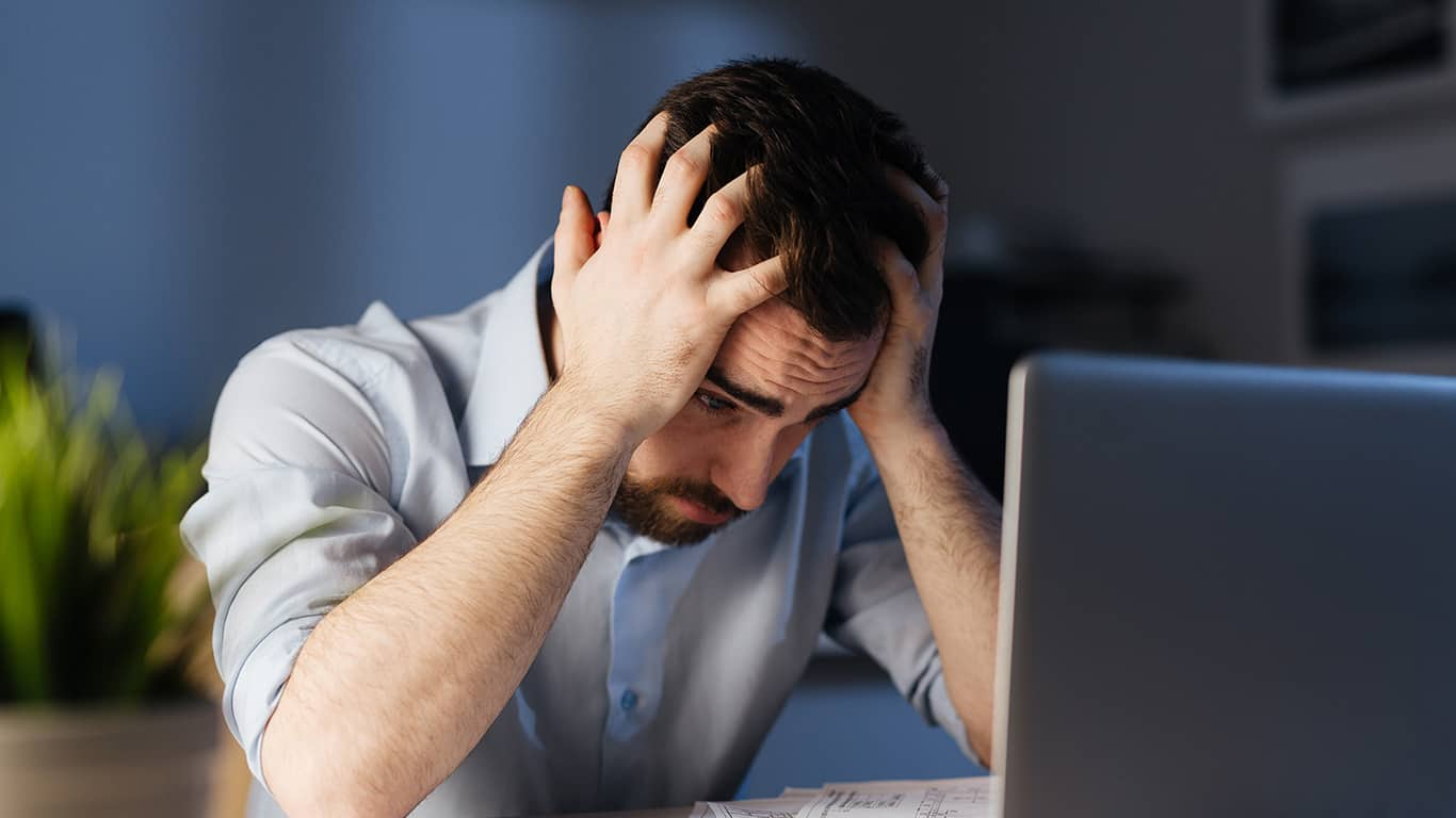 Portrait of exhausted man working overtime with documentation and laptop alone in dark office late at night, clasping head with hands looking stressed