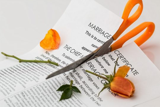 divorce and debt; scissors cutting divorce papers and a rose