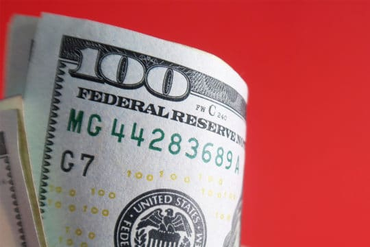 A white ceramic cup with cash dollars money inside on red background