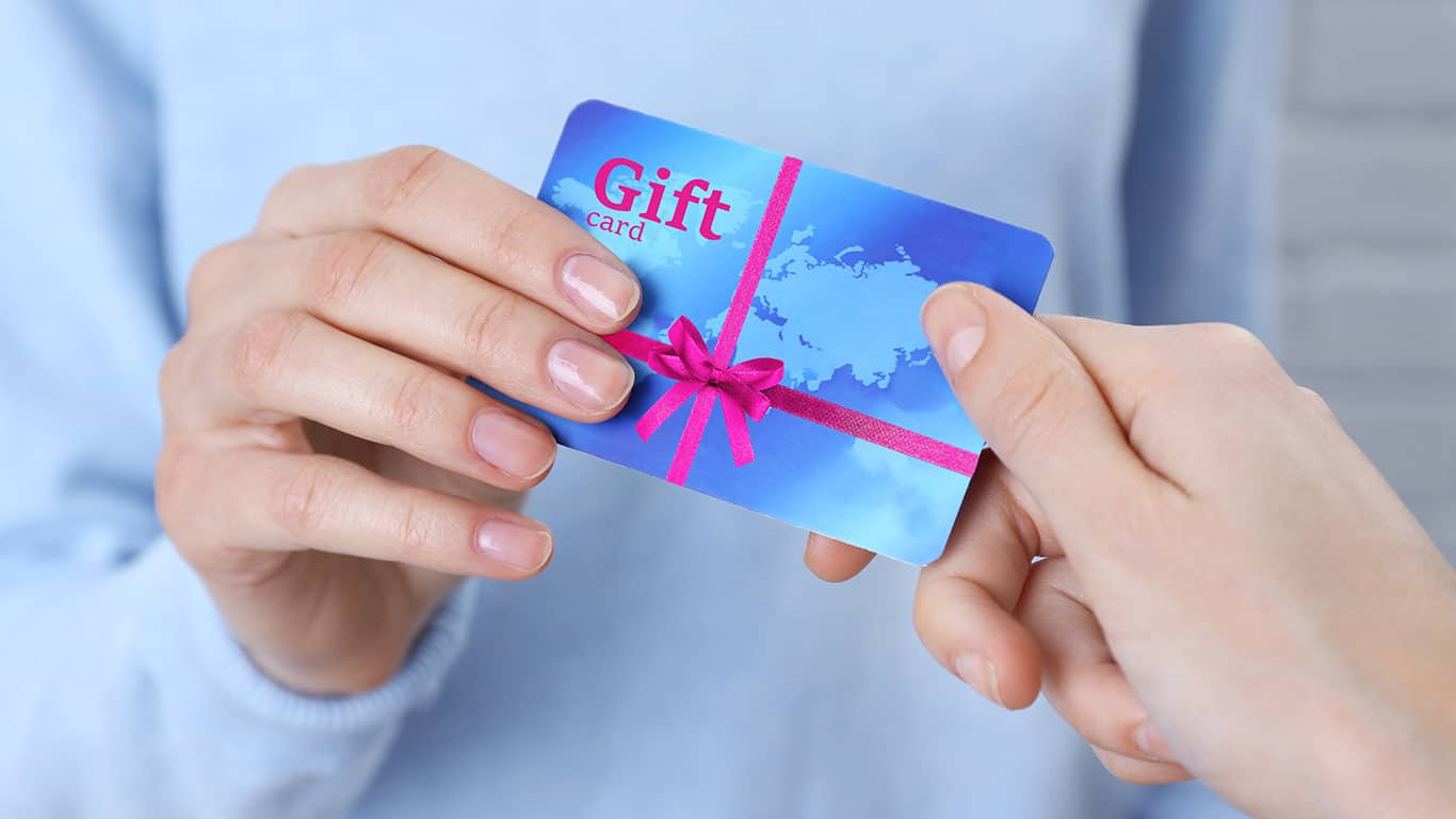 Woman giving gift card to friend, closeup. Holiday celebration concept
