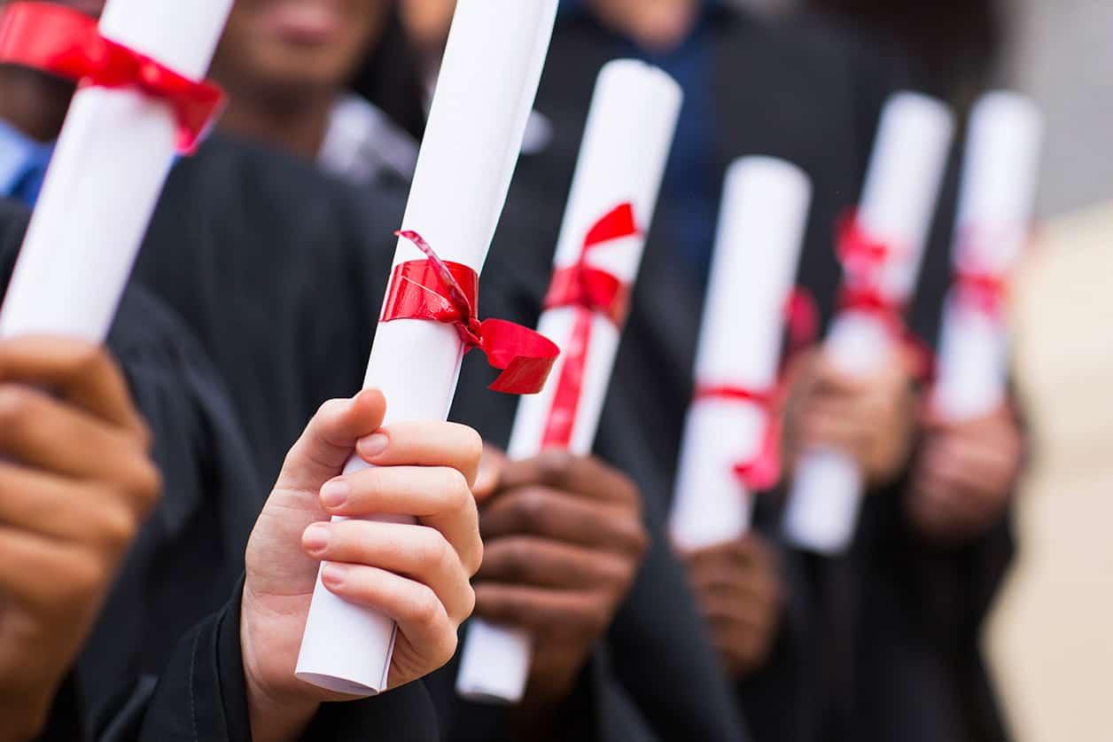Group of multiracial graduates holding diploma