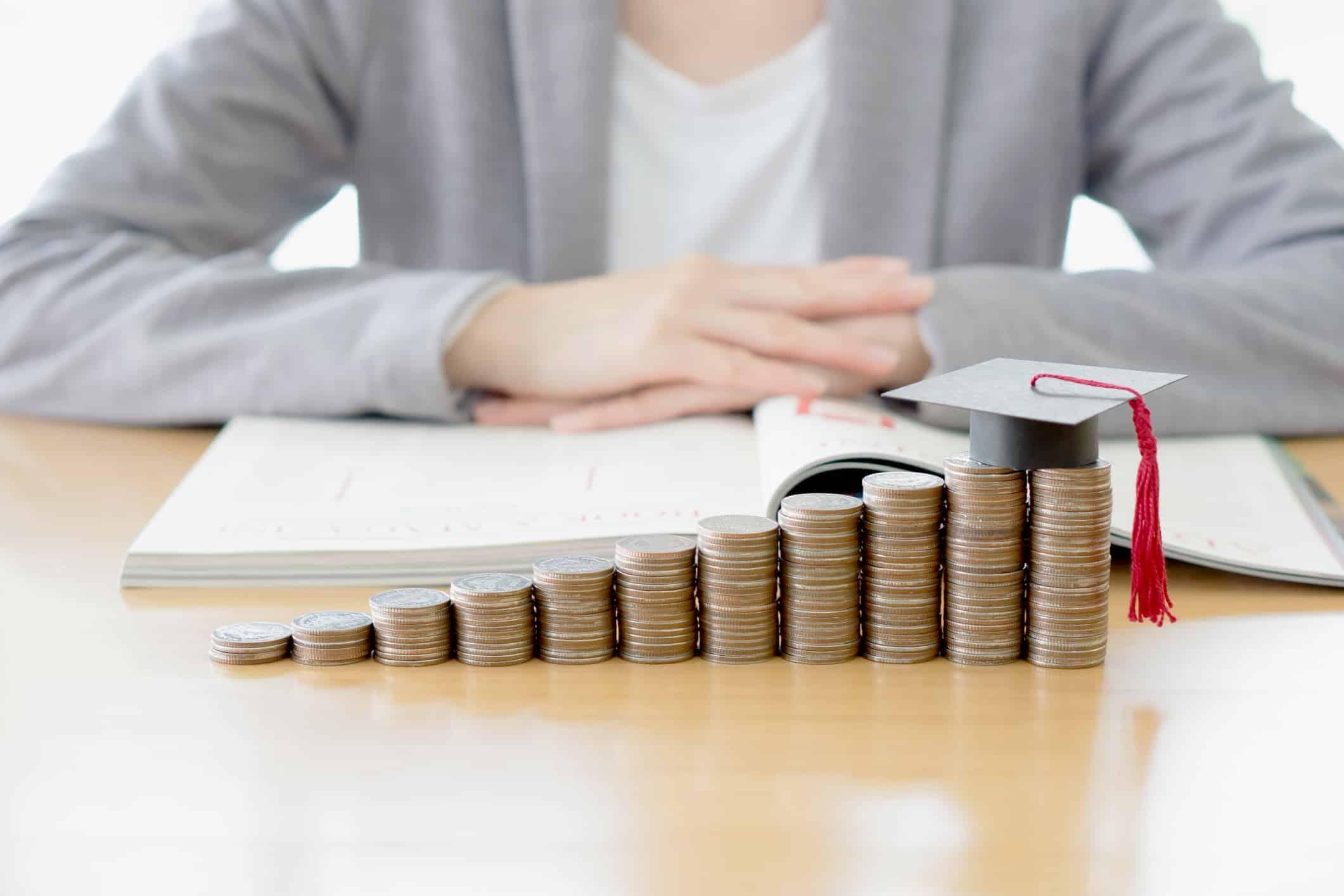 graduated repayment plan; Businesswoman saving education coins
