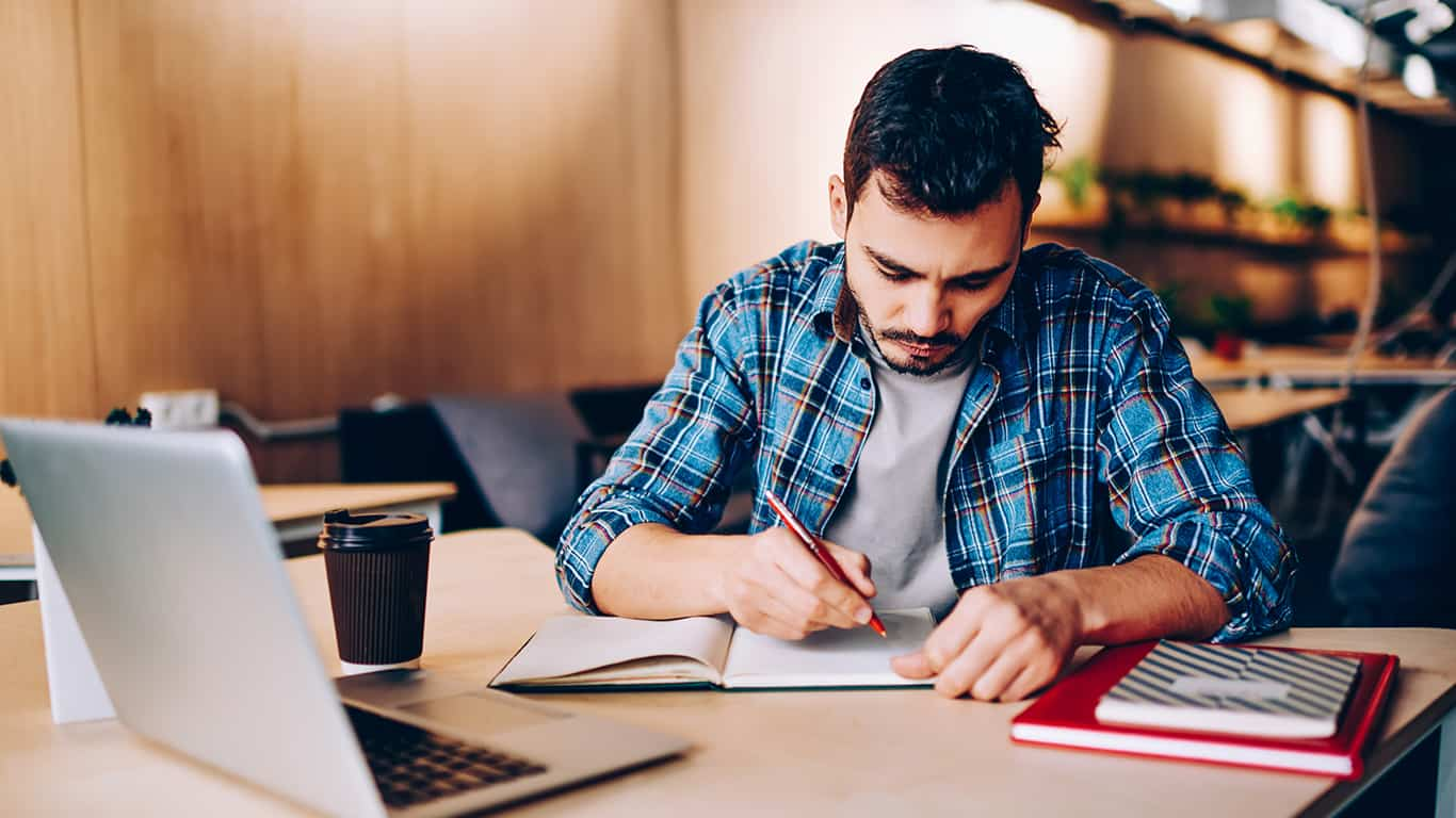 Serious young male student writing essay