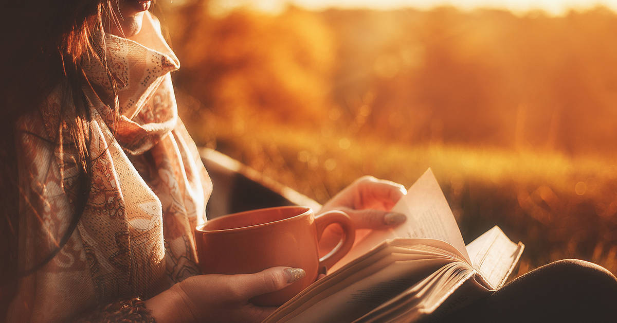 Beautiful girl in autumn forest reading a book covered with a warm blanket.