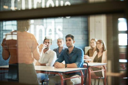 deuda de préstamos estudiantiles de statistics, affording a higher education; Shot of a group of businesspeople sitting in the boardroom during a presentation