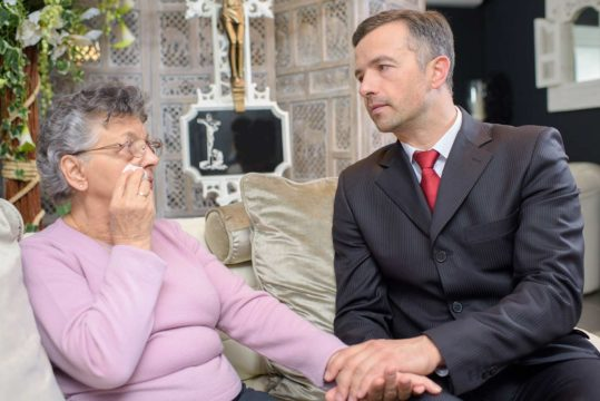 how much does a funeral cost?; older woman talking to a funeral home worker