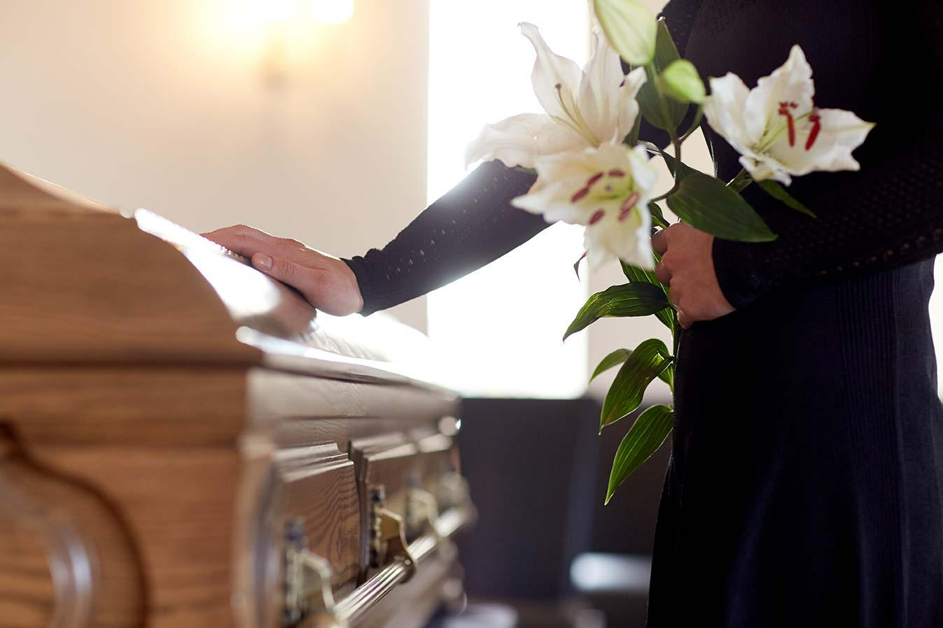 help with funeral costs; person with flowers touching a casket
