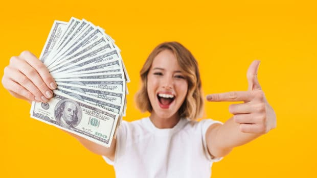 Excited blond woman in basic t-shirt holding bunch of money