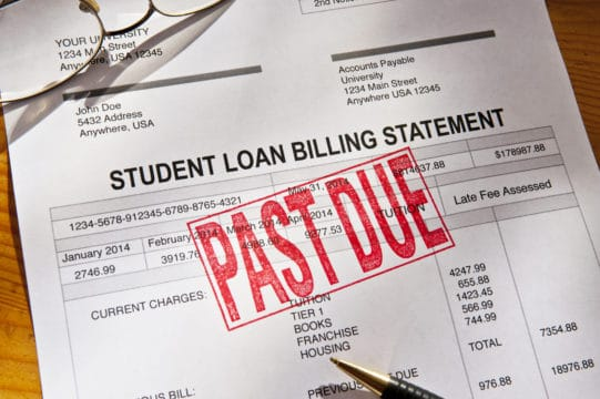 student loan debt statistics, student loan default; Statement for a Student Loan on a desktop. Loan is PAST DUE with a red rubber stamp. Props include reading glasses, coffee cup and pen. Horizontal photograph. PAST DUE is bright red against the white form. Shot from a high angle looking down. Dramatic lighting with some shadows.