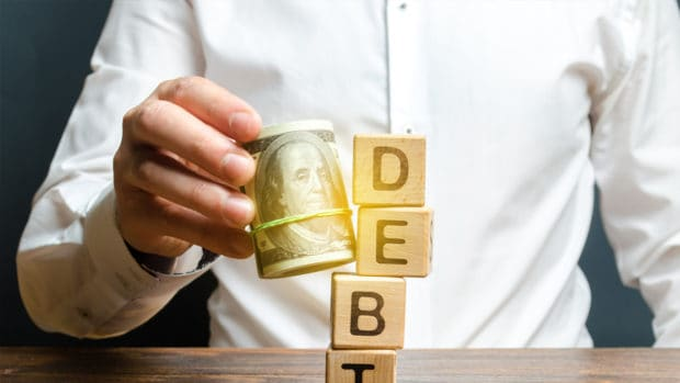 A man knocks down the tower with the word debt