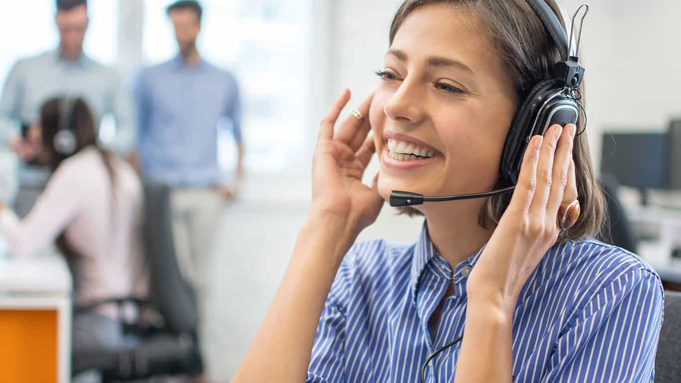 Portrait of beautiful friendly female customer services agent with headset working in call center