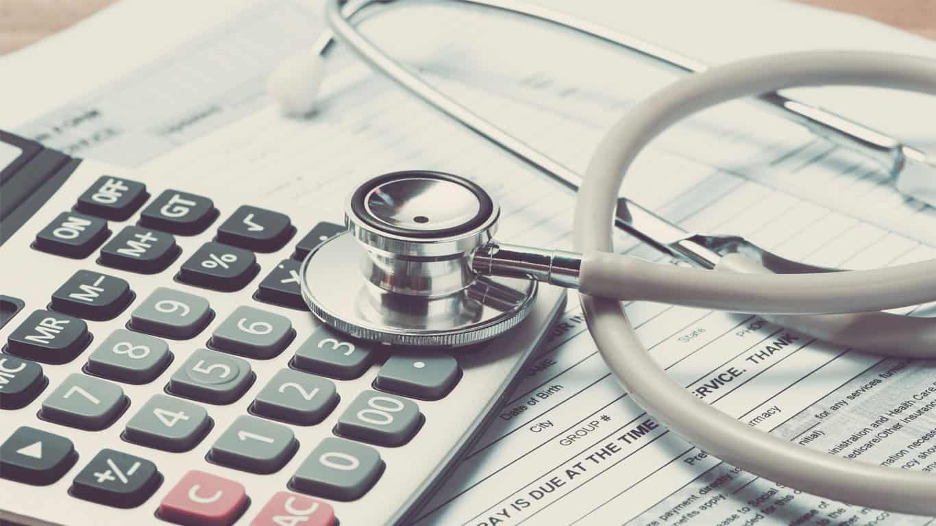 do medical bills affect your credit; stethoscope on top of calculator and medical bills
